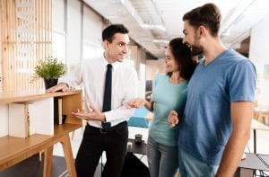 furniture salesman showing a couple a shelving unit with books in it