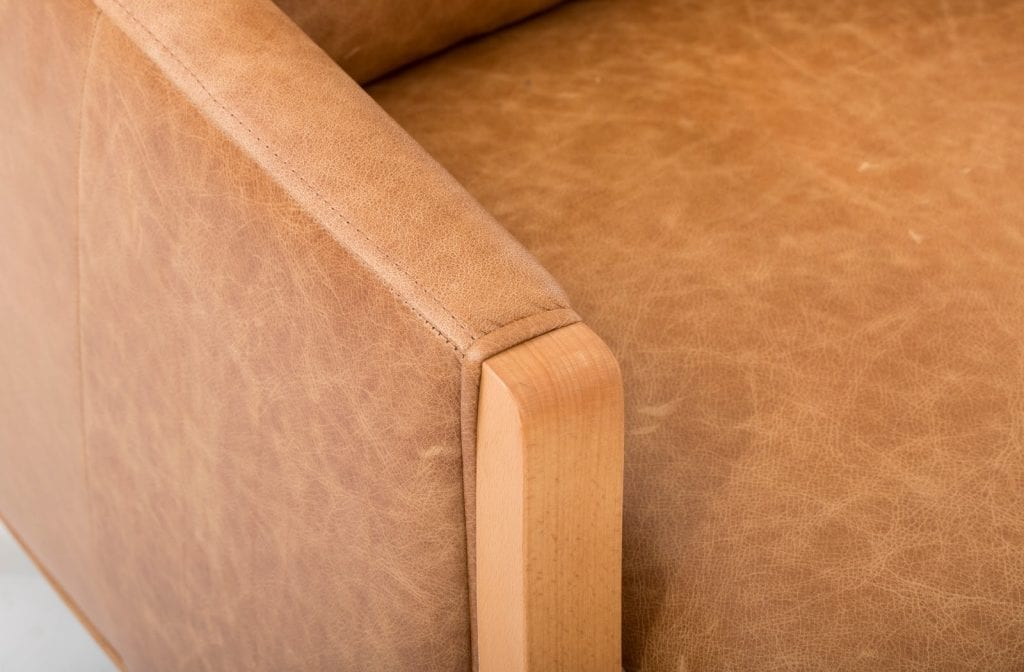 A top-grain brown leather couch with wooden legs