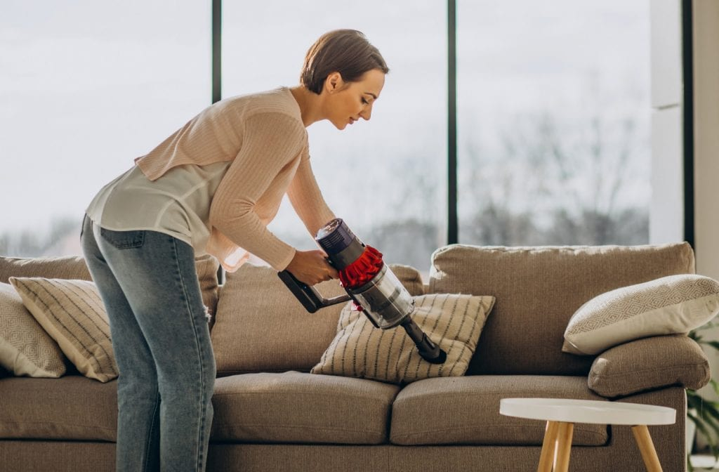 Woman cleaning her sofa with portable vacuum in her house