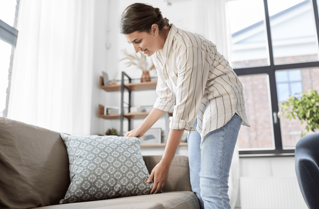 Woman happily adjusting cushions on her sofa.