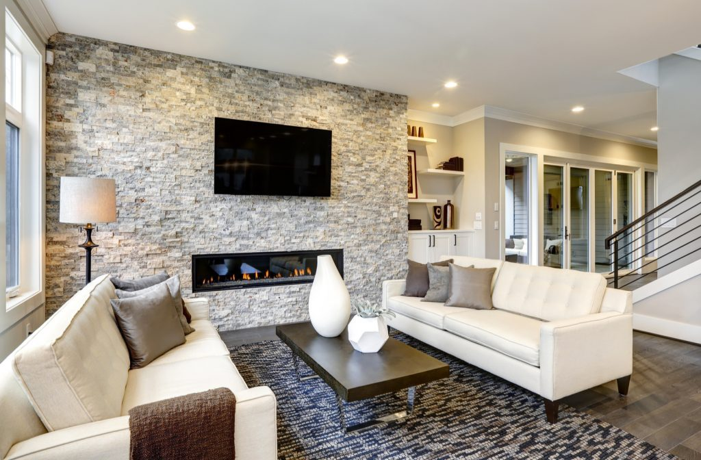 Living room furniture layout with soft color sofas and brick style fireplace.