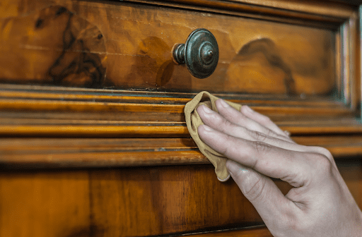Close up of hand using cloth to clean wooden closet door