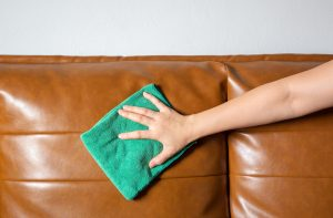Hand cleaning leather sofa using soft cloth