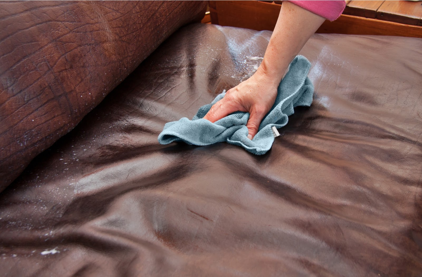 Hand using soft cloth to clean dirty leather sofa